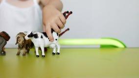 Los padres enseñan a un pequeño niño a distinguir entre animales, un juego del ` s del niño con los juguetes y padres, primer, ca almacen de video