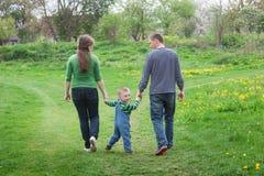 Los padres están caminando con un niño pequeño en un prado verde de la primavera en un sendero Imágenes de archivo libres de regalías