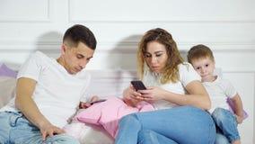 Los padres est?n mirando en sus tel?fonos m?viles que no prestan la atenci?n a su ni?o Escape de la realidad, dependencia de foto de archivo libre de regalías