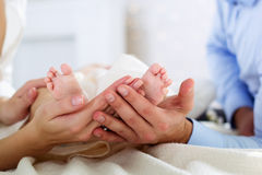 Los padres están deteniendo al bebé se alzan por las manos Imagenes de archivo