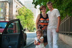 Los padres felices acercan a un nuevo coche Foto de archivo libre de regalías