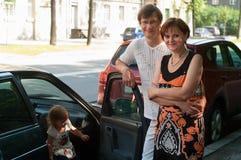 Los padres felices acercan a un nuevos coche y niño aquí Fotos de archivo libres de regalías