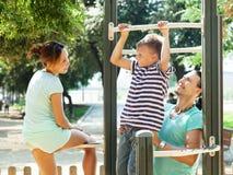 Los padres felices con el entrenamiento del hijo encendido levantan la barra Foto de archivo libre de regalías