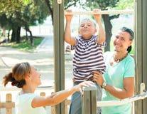 Los padres felices con el entrenamiento del niño con levantan la barra Foto de archivo libre de regalías