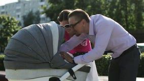 Los padres felices jovenes son de abrazo y que se besan que se coloca con un cochecito para un recién nacido metrajes