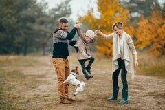 Los padres felices se divierten con su hija en la trayectoria de bosque t siguiente imágenes de archivo libres de regalías