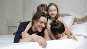 Los padres felices y dos niños de risa están mintiendo en la cama blanca que se divierte juntos durante fin de semana en casa her almacen de video