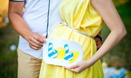 Los padres futuros sostienen la placa con una inscripción cerca de un estómago Fotos de archivo libres de regalías