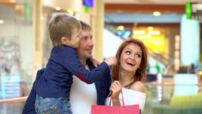 Los padres hablan con el hijo en la alameda comercial La familia ha hecho las compras para la Navidad en centro comercial Padres  almacen de video