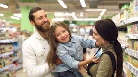 Los padres hermosos y su hija están eligiendo los dulces en supermercado almacen de metraje de vídeo