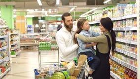 Los padres hermosos y su hija están eligiendo los dulces en supermercado MES lento almacen de video