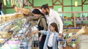Los padres hermosos y su hija están eligiendo los dulces en supermercado MES lento almacen de metraje de vídeo