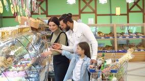 Los padres hermosos y su hija est?n eligiendo los dulces en supermercado almacen de metraje de vídeo