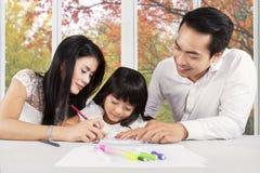 Los padres jovenes ayudan a su estudiar del niño Fotografía de archivo