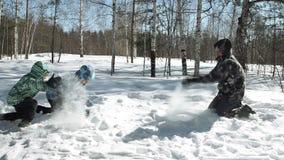 Los padres jovenes con el hijo están jugando en nieve metrajes