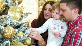 Los padres jovenes con la hija del ni?o pusieron el ornamento en el ?rbol de navidad en casa metrajes