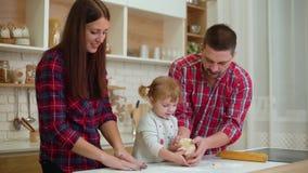 Los padres jovenes con la hija del niño se divierten junta que amasa la pasta almacen de video