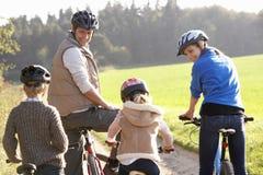 Los padres jovenes con los niños montan las bicis en parque Fotos de archivo