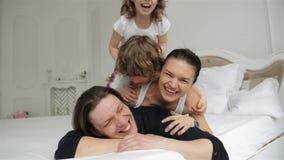 Los padres jovenes con sonrisas encantadoras están pasando tiempo libre con su hijo e hija en el dormitorio por la mañana almacen de metraje de vídeo