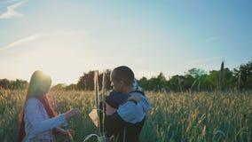 Los padres jovenes con una pequeña hija en el campo entre las espiguillas verdes del trigo disfrutan de la puesta del sol Tomarla almacen de metraje de vídeo