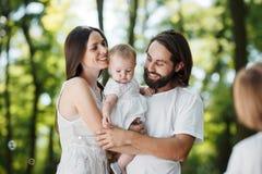 Los padres jovenes de risa vestidos en la ropa blanca están celebrando la hija en los brazos y la mirada allí del hijo fotos de archivo libres de regalías