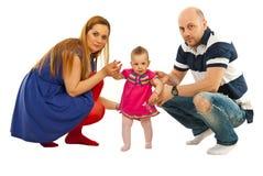Los padres jovenes detienen al bebé para hacer los primeros pasos de progresión Foto de archivo