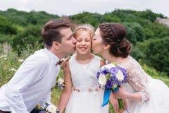 Los padres jovenes en vestidos de boda besan a su hija joven en mejillas foto de archivo