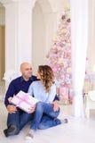 Los padres jovenes enamorados en la Navidad festiva del intercambio del humor presen Imagen de archivo libre de regalías