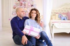 Los padres jovenes enamorados en la Navidad festiva del intercambio del humor presen Imagen de archivo