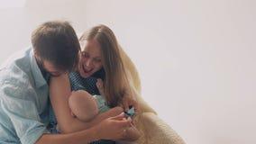 Los padres jovenes felices hermosos sonríen a su madre recién nacida preciosa del hijo que calma a su bebé en una mecedora 4K almacen de metraje de vídeo