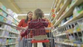 Los padres jovenes hermosos y su pequeña hija linda están sonriendo mientras que eligen la comida en el supermercado La muchacha