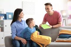 Los padres jovenes que ayudan a su pequeño niño consiguen listos imágenes de archivo libres de regalías