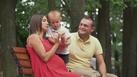 Los padres jovenes se sientan con un hijo del bebé en un banco de parque almacen de video