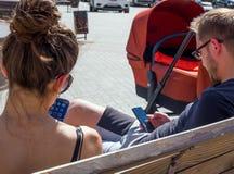 Los padres jovenes se sientan en el banco de parque olímpico con los teléfonos en sus manos fotos de archivo libres de regalías
