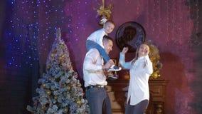 Los padres jovenes y su niño bailan cerca de un árbol de navidad almacen de metraje de vídeo