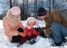 Los padres juegan con el niño en parque del invierno Imágenes de archivo libres de regalías