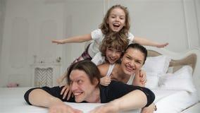 Los padres juguetones están disfrutando de fin de semana con su hijo e hija que ponen en la cama blanca Pares jovenes con los niñ metrajes