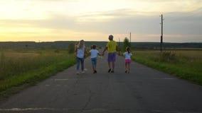 Los padres maduros con tres niños van a lo largo del camino en campo La familia feliz se divierte en la naturaleza Viaje, turismo almacen de metraje de vídeo