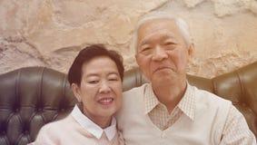 Los padres mayores de Rich Asian se sientan en backgrou hermoso de lujo de la casa imagen de archivo libre de regalías
