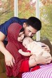 Los padres musulmanes felices besan a su niño Foto de archivo libre de regalías