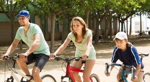 Los padres positivos con el montar a caballo del niño montan en bicicleta en parque Imagen de archivo