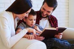 Los padres preciosos comparten tiempo especial con el niño mientras que leen en fotografía de archivo libre de regalías