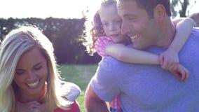 Los padres que dan a niños llevan a cuestas paseos en jardín metrajes