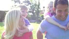 Los padres que dan a niños llevan a cuestas paseos en jardín almacen de metraje de vídeo