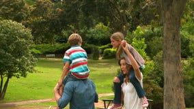 Los padres que dan a sus niños llevan a cuestas paseo almacen de video