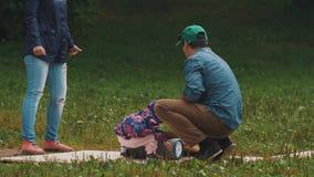 Los padres que miran como el niño del niño del bebé observan al tablero en un cilindro metrajes