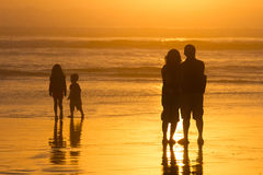 Los padres que miran a niños juegan las siluetas, puesta del sol en la playa Fotografía de archivo libre de regalías
