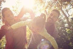 Los padres se divierten con la hija afuera En el movimiento Foto de archivo libre de regalías