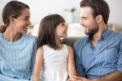 Los padres sonrientes relajan hablar con poca hija fotografía de archivo libre de regalías