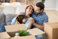 Los padres sonrientes se relajan con la hija en el sof? casero imágenes de archivo libres de regalías